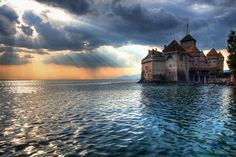 Chateau de Chillon, Veytaux, Switzerland.  Perched on the shored of Lake Meman, this castle was the subject of a famous poem by Lord Byron, the Prisoner of Chillon. The 17th century poet even carved his name into a pillar in the castles dungeon.