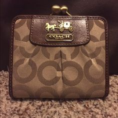 COACH KHAKI W/LEATHER TRIM WALLET, NICE! COACH KHAKI W/LEATHER TRIM WALLET, NICE! This has the coin brass closure snaps like on a coin purse. It's a bi-fold wallet with light pink color inside and lots of pockets for different cards and money slots. In used condition but good used condition. Has a lot more love to give! No visible stains that I can see. May just need some light cleaning. But it's in very good condition otherwise! It's very sturdy and the perfect size! Coach Bags Wallets