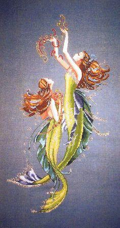 Two daughters of the sea swim gracefully toward treasure lost.