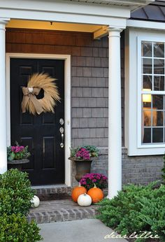 Our Front Door by Dear Lillie - a classic fall porch with pumpkins, mums and a wheat wreath.