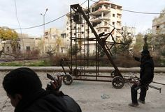 A Free Syrian Army fighter uses a catapult to fire a homemade grenade at Syrian Army soldiers during a fight in the Arabeen neighborhood of Damascus, on January 24, 2013. (Reuters/Goran Tomasevic) #