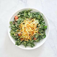 Kale and black bean salad with avocado jalapeño dressing and crispy spiralized shoestring potatoes. Vegan and gluten-free.