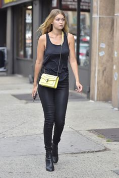 in New York during the first day of New York Fashion Week, wearing black head to toe and a yellow Bulgari bag.    - HarpersBAZAAR.com