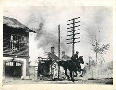 1941- German dispatch rider gallops through burning Soviet town under enemy artillery fire.