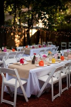 Simple white tables with bright favors at the place settings make this backyard vow renewal picture perfect