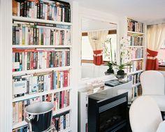 Bookcase Shelving - Books arranged on white built-in shelves beside a modern fireplace