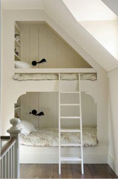 The third floor of the home is the children's domain. Influenced by train bunk beds, the architects designed a row of three built-in beds, each lit with a marine-style sconce and closed off with curtains.