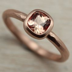 Our 5mm Rustic Cushion Cut Solitaire Engagement Ring with a Light Peach Chatham Padparadscha Sapphire in 14k Rose Gold.