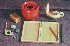 Roman writing materials 44 BC to AD 400, a metal stylus and wax tablet used for writing on.To the right of the wax tablet is wax and an intaglio ring for making seals and seal boxes to protect them.At the top are thin wooden writing tablets which could be written on with ink from the ink pot at the top left. This type of tablets do not usually survive but around 1000 of them were found preserved at Vindolanda, near Hadrian's Wall; Verulamium Museum, St.Albans, Hertfordshire, UK