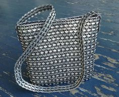 This bag was handcrafted by women in villages in Mexico. Aluminum tabs are collected from soda machines in schools and universities and recycled into this beautiful purse. This bag is 10 wide and 11 tall and woven together with black cording. The strap is 46 long and long enough to be worn across your body if you prefer. It is very lightweight, has zip closure and one small inside zip pocket. This is a fair trade item. Artisans receive a fair price and work in safe conditions while providing…