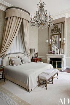 The bed in the master suite is highlighted by an 18th-century corona and a Louis XV bench; the chandelier is 1880s Italian, and 1940s Jansen sconces flank the Louis XVI trumeau.