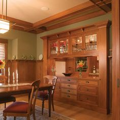 Rich Mahogany Wood takes center stage in this Traditional Dining Room with an Arts & Crafts Chandelier which highlights the warm tones and superior finish of the built-in cabinetry. LOVE THE POCKET DOORS~!!! ~ Craftsman Style Kitchen Cabinets Design, Pictures, Remodel, Decor and Ideas