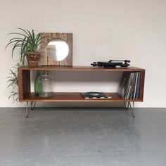 This classic mid-century style console table is ideally sized for use as a vinyl record storage cabinet, but it can also be used as a media unit, sideboard or coffee table. It is hand made from high quality softwood timber and is fitted with Eames style hairpin legs for a classic Nordic chic look. This unit is fine sanded, stained and sealed with an oil stain and a low-sheen, natural look, hardwearing finish. - Colour Options: Colours Available: - Antique Pine (as shown) - Dark Oak (as…