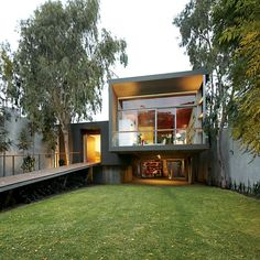 This contemporary home in Lima, Peruwith a sweeping grass driveway wrapsaround existing trees in its central courtyard.