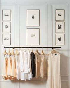 Camisoles and blouses hang below a vintage gallery wall in the 5th Avenue shop of @Club Monaco .