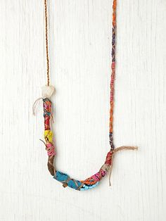 Mixed Media Necklace, Colorful multi-fabric and textured necklace made up of different colored thread, beads, sequins, crochet pieces, and leather strands. Crystal stone detailing. Ties around neck.