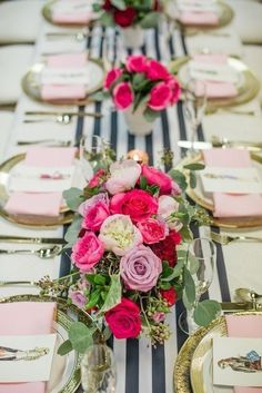 A striped wedding table runner with pink wedding centerpieces including white peonies and roses for a modern wedding tablescape.