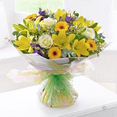 Spring Sunshine Hand tied - We've chosen the colour of the season – golden sunshine yellow – as the inspiration for this stylish gift. These exquisite lilies and germini are contrasted with rich purple lisianthus, giving depth to an attractive display. The velvety roses add a hint of luxury too. #Spring #Flowers