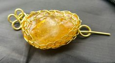 Gold Viking Knit wrapped citrine pin. Can be worn on anything knitted (hats, scarfs, or sweaters.)