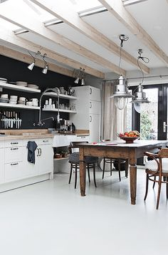 white and wood, modern combined with old and rustic table, open shelving, spot lights from the ceiling to the kitchen counter, big hanging lamps over dining table, big industrial kitchen style tap