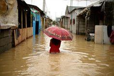 Manila, Philippinen: Kopfschutz  (20.12.15)   Ein Mädchen mit Regenschirm watet durch die...