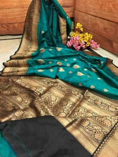 This fabulous Deep Teal color Silk Mark Certified pure Katan Banarasi is exclusively crafted and handpicked for you to adorn on special occasions. The fine Golden Zari weaving done in timeless Banarasi style gives an ethnic look. Contrasted with Zari weaved marvellous Black color border and pallu this pure silk saree i