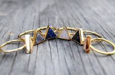 *Strong geometric design combines with super sparkly druzy stone, these gold-plated rings are a great statement ring.  *The druzys are available in three colors: black, brilliant gold, and rose gold  *Each druzy is unique, and variances in shade is possible with this type of stone. *These rings are available in sizes between US 5.5 and 7. This is not an adjustable ring. It is 18K gold plated over copper. The stone size is 12mm x 11mm (1/2). *These unique rings make great gifts, and will be…
