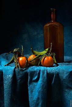 Tangerines with brown glass bottle, photo  by...?