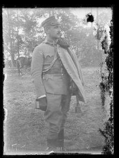Klisza przedstawia oficera pułku ułanów Legionów Polskich - mężczyznę w średnim wieku, stojącego na tle drzew widocznych w oddali, zwróconego 3/4 ku prawej, ujetęgo poniżej kolan, z bliskiego planu, w pionowym kadrze. Oficer ubrany jest w kurtkę mundurową i ułankę z futrzanym kołnierzem zarzucona na lewe ramię, bryczesy wpuszczone w cholewy butów i w czapkę maciejówkę z orzełkiem legionowym. Na dłoniach ma ciepłe rękawice. Twarz o regularnych rysach, z prostym nosem, ciemnymi, krótko prz... Statue, Art, Art Background, Kunst, Performing Arts, Sculptures, Sculpture, Art Education Resources, Artworks