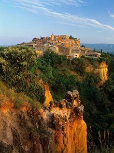 Roussillon, Vaucluse, Provence, França   Vermelhas como as colinas cor de ocre circundantes, as casas de Roussillon refletem os muitos tons diferentes desta paisagem impressionante.   O pôr do sol é um momento perfeito para se banquetear com esta sinfonia de cores, que varia do amarelo ao vermelho.