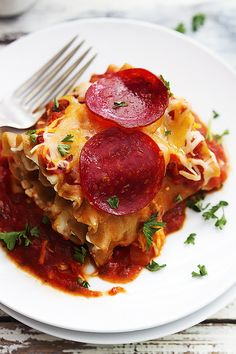 Pepperoni Pizza Lasagna Roll Ups are so easy to make!! Classic pepperoni pizza and lasagna get smashed together in this tasty hybrid dish!