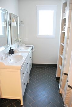 Found the perfect gray paint colour (`Runway Coach`by PARA Paints) for this bathroom. Herringbone floors, white Hemnes IKEA vanities, chrome fixtures, and West Elm shower curtain.