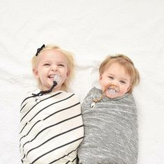 Cute girls breaking in swaddle blankets for their baby brother.