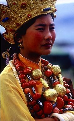 Khampa Tibetan Girl from wealthy family wears gilded crown headdress and necklace as well as coral, dzi and ivory beads and bracelets at Litang Horse Festival circa 1998