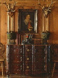 Antlers over a French chest and oil painting...the paneling is gorgeous and the little side chairs are very interesting.