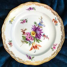 A different bouquet of summer flowers in the center surrounded by meadow blossom and richly embellished with a gold filigree rim on each of the eight plates. A common thread is a prominent purple colored blossom on each one.   eBay!