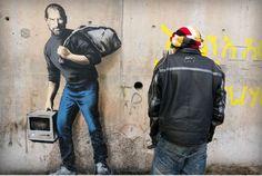 Ein Apple-Rechner in der Hand, ein Müllbeutel auf dem Rücken: Banksy hat ein neues Graffito geschaffen, das auf die Herkunft von Steve Jobs' Vater hinweist, der syrischer Migrant war. Er kommentiert so die Flüchtlingskrise.