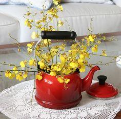 Quer descontrair? Crie um vaso novo para a sua flor. Esta chuva-de-ouro ficou charmosa dentro de uma chaleira esmaltada vermelha