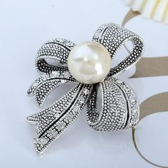 This Ribbon Pin Brooch showcases a textured silver rhibbon with pearl center and rhinestones detailing. Crafted in antique silver overlay, the Vintage Rhinestones Pearl Ribbon Pin Brooch is secured with standard pin clasp.