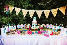 mesa de doces com bandeirolas para festa infantil para meninas tema animais da floresta em tons de azul, rosa e dourado.