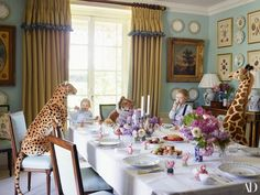 Nancy and Billy Naylor-Leyland indulge in sweets in the dining room of Stibbington House. The windows are curtained in a Claremont fabric, edged with Samuel & Sons tassel fringe, and a Thibaut wallpaper covers the walls. 18th-century chairs in a Colefax and Fowler silk; toy animals from Selfridges | archdigest.com