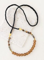 The long Masuma Necklace combines braided black suede, faceted labradorites and gold-tinged mala beads.