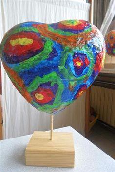 ballon in hartvorm beplakt met krantrepen, laatste laag wit papier. Als alles droog is beschilderen. Gaatje onderaan ballon knippen en over stok steken. Een mooi kunstwerkje voor moederdag!