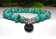 "This beautiful turquoise engraved bracelet is made with Turquoise Czech beads with a Picasso finish and 6mm Turquoise Howlite with a stainless steel charm engraved with ""Breathe"". Great color. Howlite"