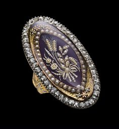 Gold and silver ring, the hoop widening at the shoulders to support the elongated oval bezel centred on a seed pearl bouquet of mixed flowers and ears of barley tied with a ribbon, applied to a royal blue enamel ground, bordered with pearl, outlined in gold leaves and flowers, with in an old-cut diamond border  Circa 1770