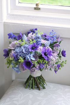 Wedding bouquet in blue, purple and green with anemone, roses, delphinium, muscari, hydrangea, lilac's and alchemilla. Liberty Blooms