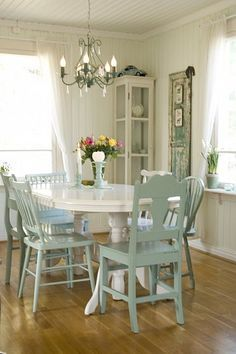 Beautiful beach cottage dining room. White painted table and aqua mismatched chairs.