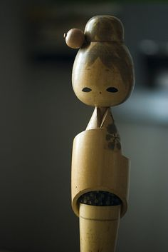I love the soft tones in the photograph and the gentle curves of this Kokeshi doll ~ La