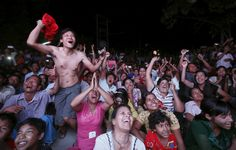 People celebrate as they watch election results roll in outside the National League for Democracy office in Mandalay, Myanmar, on 8 November
