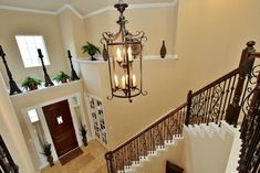 Another perspective of the Two Story Foyer shows the upscale decorator ledge, chandelier and wrought iron railing.